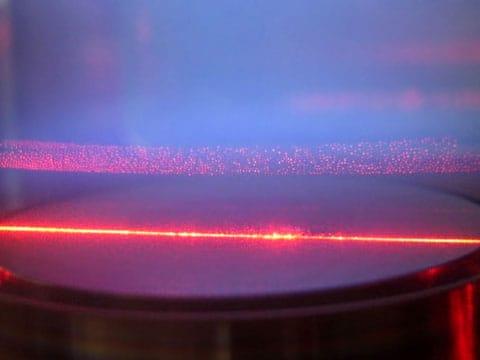 Laboratorní snímek prachového plazmatu. Tady z něho vychází namodralá záře, a červený paprsek je laser, ve kterém jsou dobře vidět prachové částice.