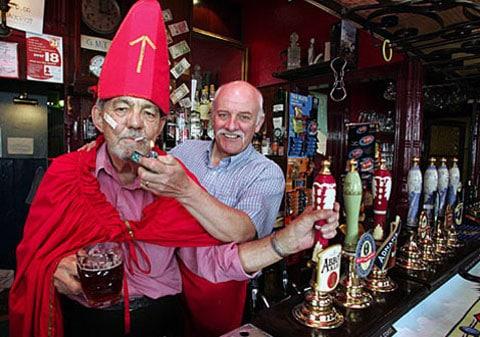 Majitel hospůdky Bob Beech (vpravo) zapaluje svému příteli a stálému klientovi Edwardovi Eldererovi. Oni dva věří, že se jim podaří jejich pivnici přeměnit na velvyslanectví a že budou kouřit dále.